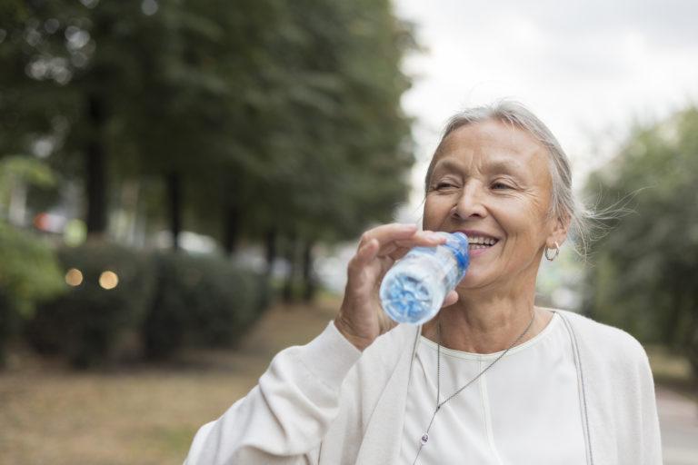 Nutricia lykkelig eldre dame utendørs drikker vann